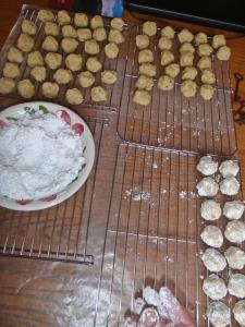 Dipping baked cookies in sugar.