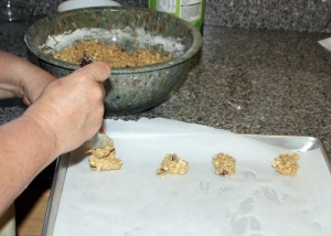 Drop cookies onto parchment lined cookie sheets by Randy Cockrell